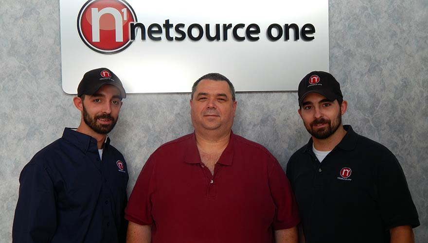 "David and Warren were hired by NetSource One, where CIO Ed French (center) says they ""have the ability to work under pressure and get the job done."""