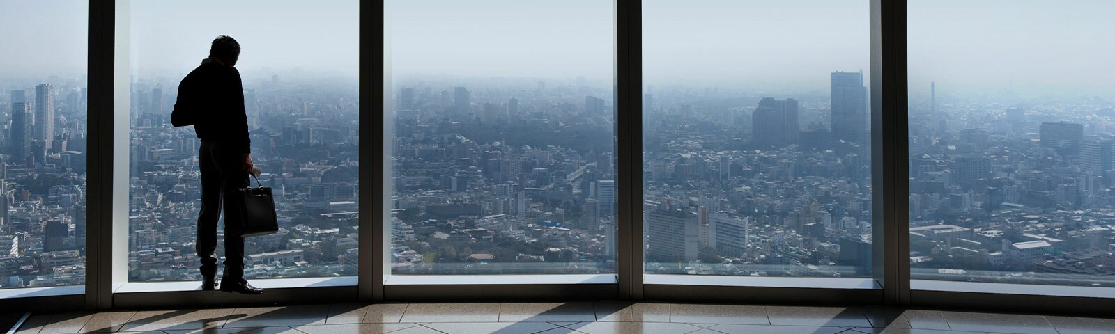 A man standing in front of big office-building windows that look out over the city