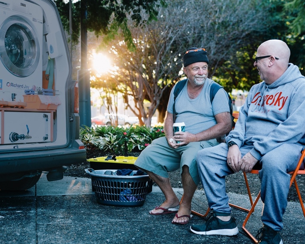 Two men sitting in park by Orange Sky washer truck
