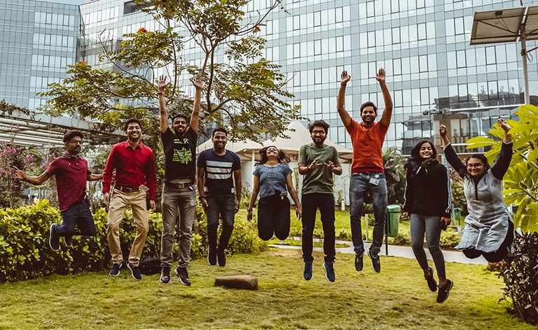 Nine engineering employees jumping in front of a Cisco building at our Bangalore, India office