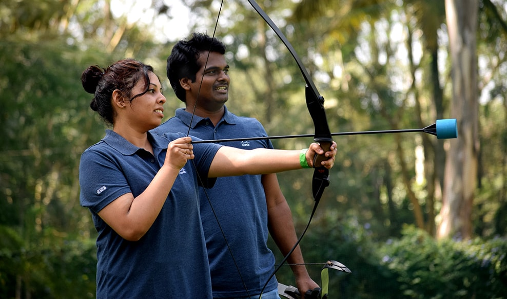 Two engineers with a bow and arrow practicing archery