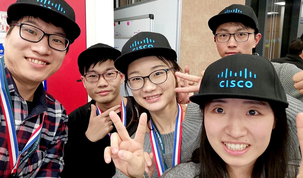 Five people smiling and wearing the same Cisco hat at our China office