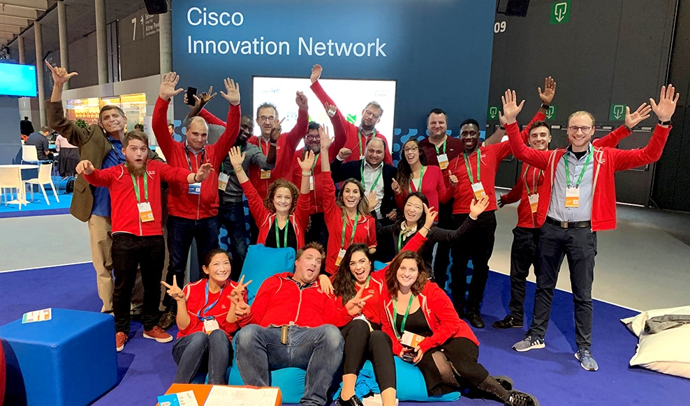Twenty engineers wearing the same red jacket raising their hands up and smiling for a group photo at Cisco event