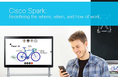 Man uses Cisco Spark on mobile phone with Cisco Spark Board in background