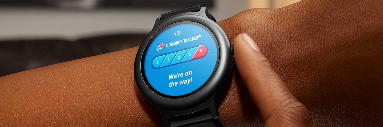 Wristwatch on person showing Domino's Tracker app