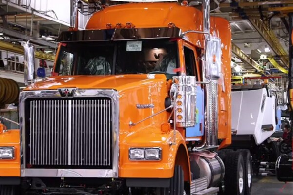Orange semi-truck rolls off the Daimler assembly line