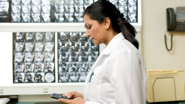 Doctor looks at mobile phone while checking scans