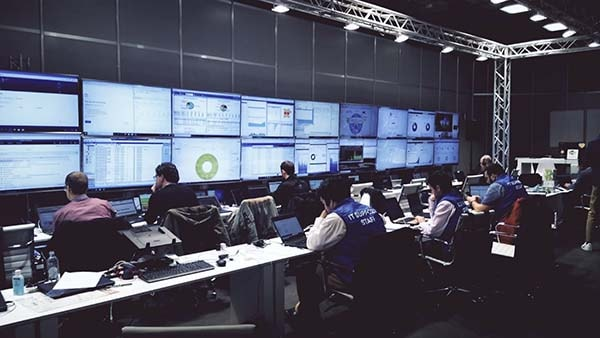 A network operations center with people working on laptops and monitoring screens