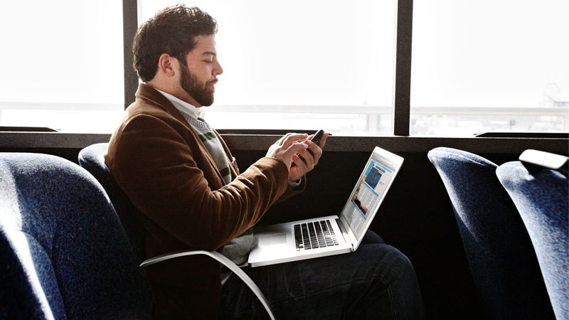 Man checks his mobile while laptop sits open on his lap in a train in Europe