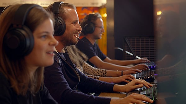 Gamers in front of computers, wearing headsets