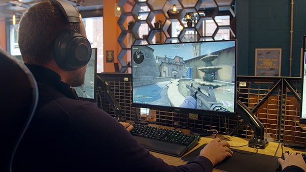 Man with headset plays video game