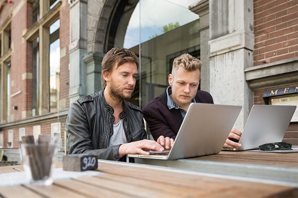 Two men work on a laptop outdoors