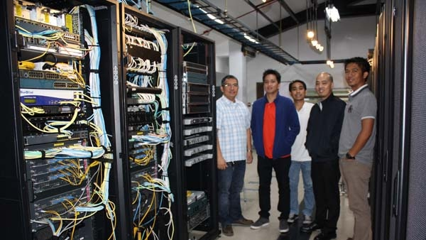 University of Santo Tomas IT employees standing next to Cisco servers in their server room