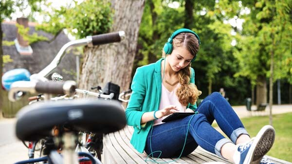 University student listens to music outdoors on her tablet using wireless connections