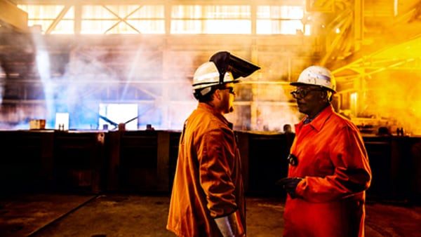 Two industrial workers in smoky environment