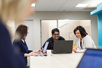 Three people smiling and looking at laptop monitor