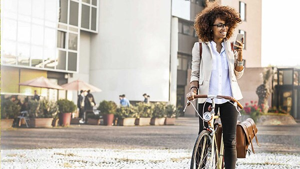 woman standing on a bike looking at phone