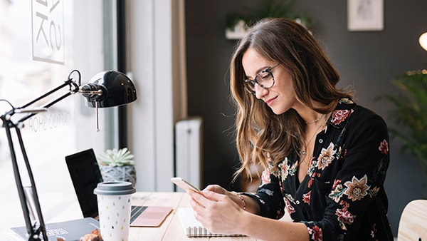 A female small business owner with long brown wavy hair in a floral black shirt looking down at her phone at her desk working from home by her laptop and the window.