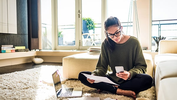 Woman, sitting on living room floor, using computer and smartphone.
