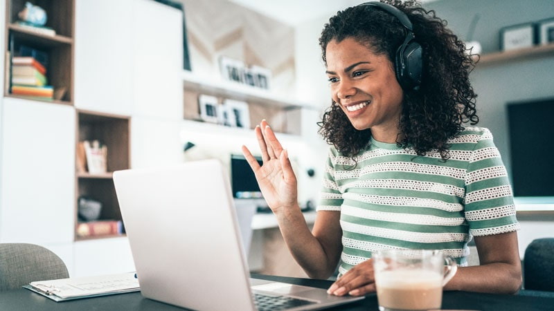 woman in home office, wearing headphones, waving at computer