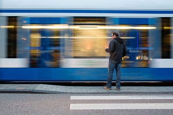 Man standing as train goes by