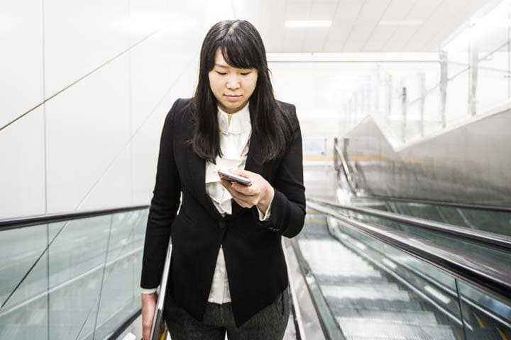 Woman checking her mobile phone while on an escalator