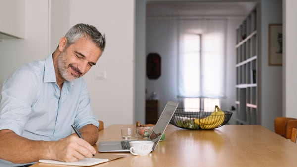 Man taking notes, in kitchen, using technology