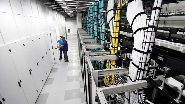 workers in a server room checking equipment
