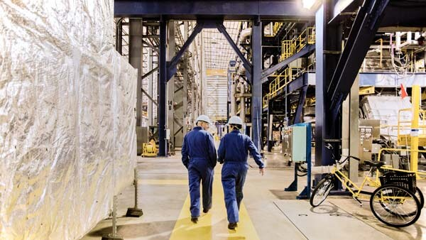 Two employees walking through a modern factory floor