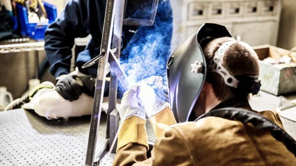 A welder works in a manufacturing facility