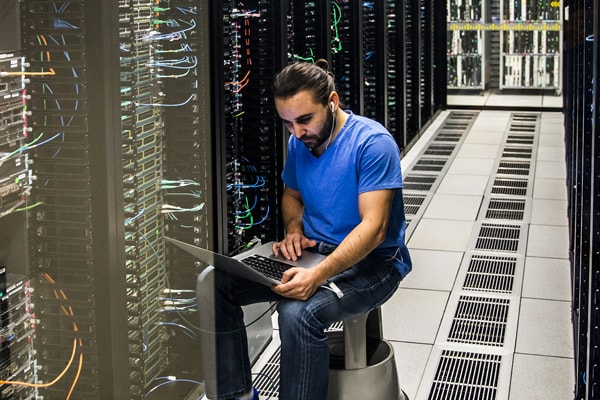 Man sitting in data center with laptop