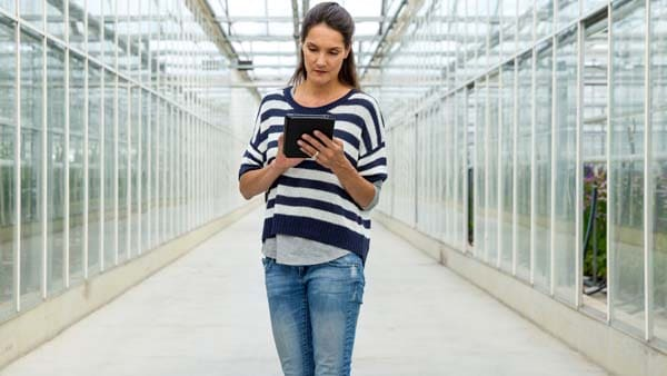 Woman walking through a data center looking at Anaconda website on her tablet