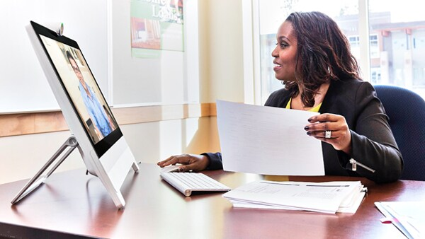 A financial advisor meets with a client by video conference.