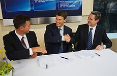 From left to right: David Helliwell, Gregor Robertson, and Scott Fawcett shake hands after they sign an MOU.